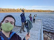 Photo of LCC's Staff and Support Team on a dock taking their hats off to show appreciation for their volunteers.