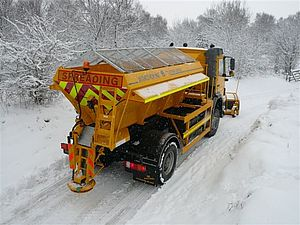 A utility truck spreading salt on a snowy road during winter.
