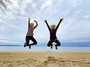 Two women jumping with joy in front of Lake Champlain.